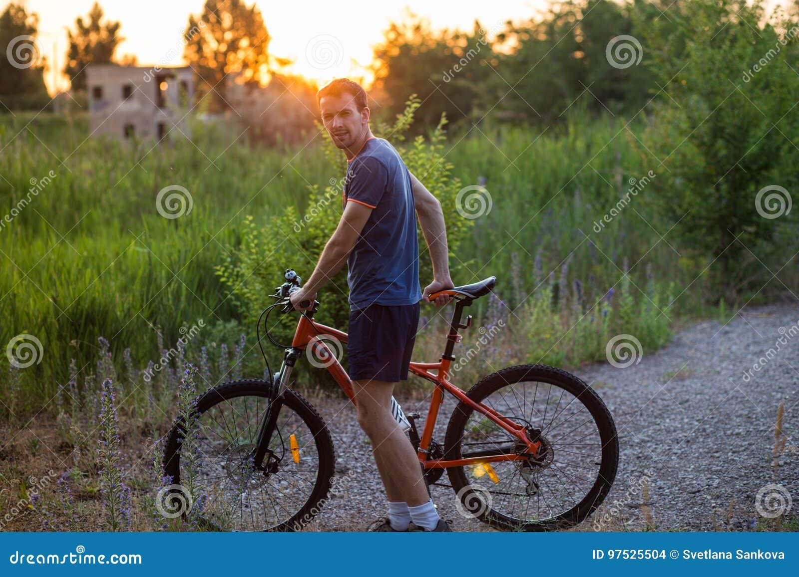 Giovane Uomo Sportivo Che Guida Una Bicicletta Al Tramonto