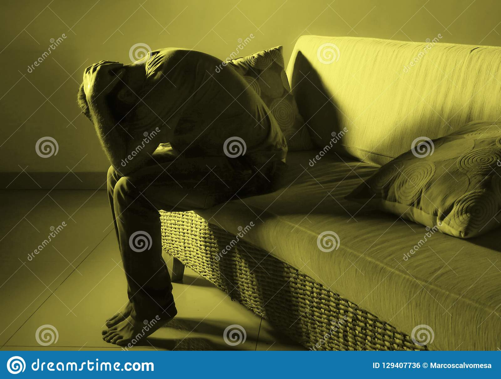 Giovane uomo triste e frustrato disperato che si addolora a casa problema di depressione dello strato del sofà e gridare di soffe