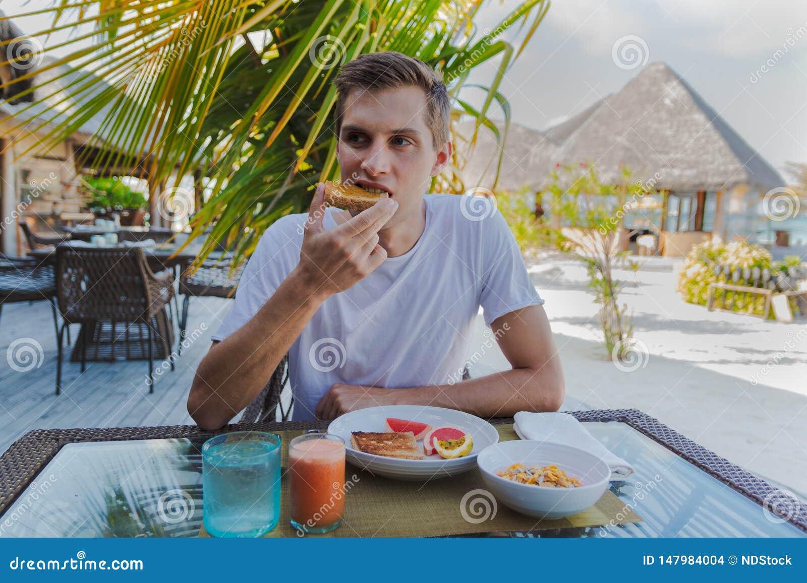 Giovane in vacanza in un isola tropicale che mangia una prima colazione sana