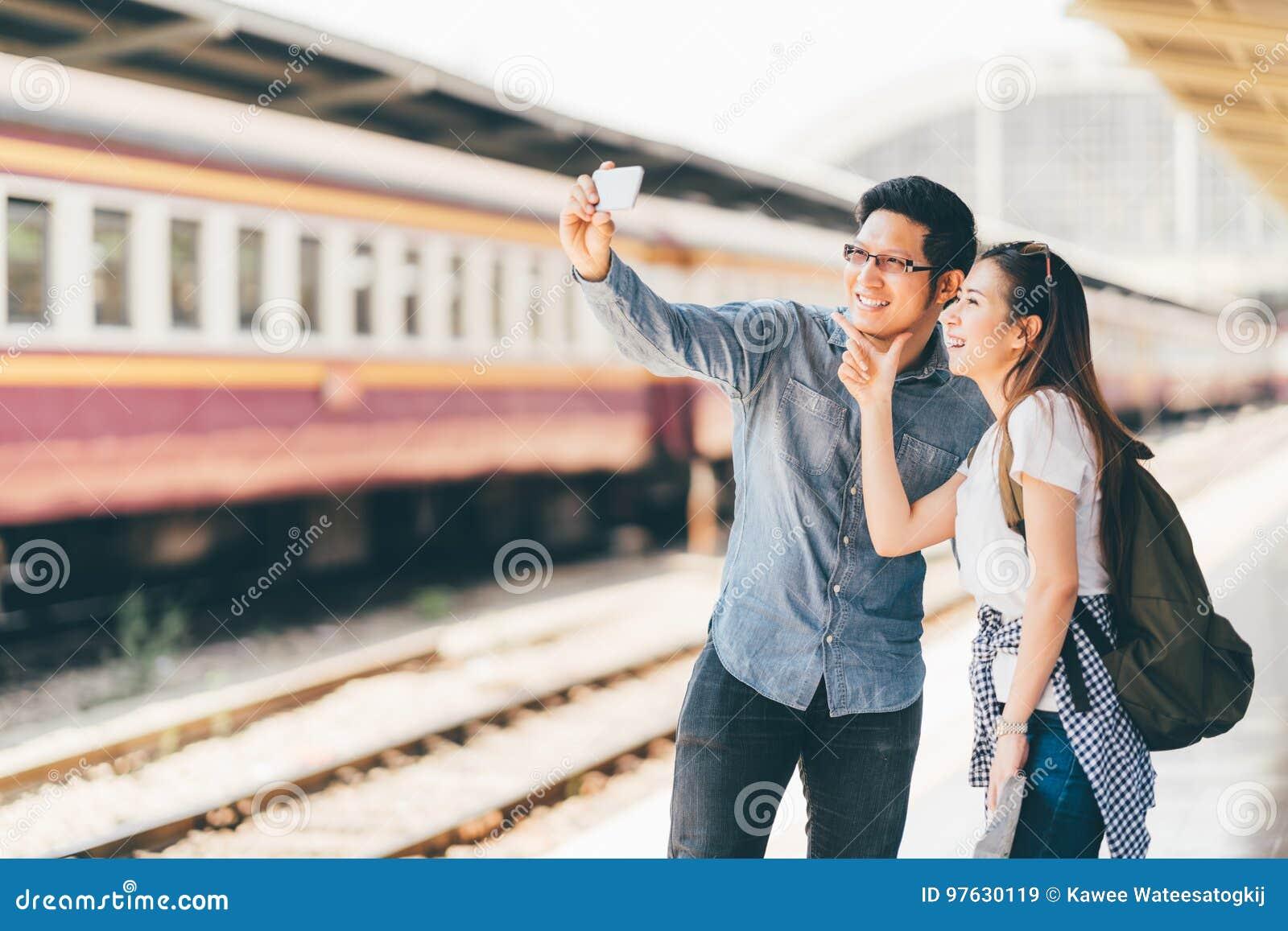 Giovane viaggiatore asiatico delle coppie che prende insieme selfie facendo uso del viaggio aspettante dello smartphone al binari