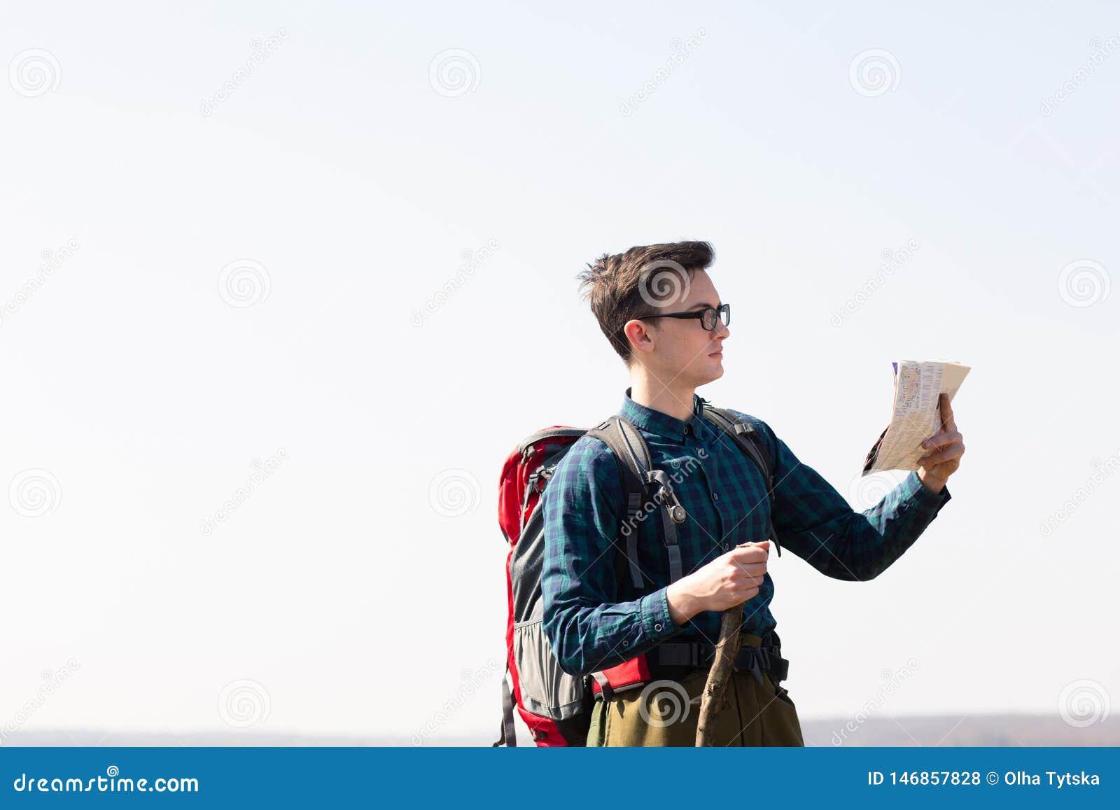 Giovane viaggiatore con lo zaino che esamina la mappa per le direzioni mentre facendo un escursione nella campagna