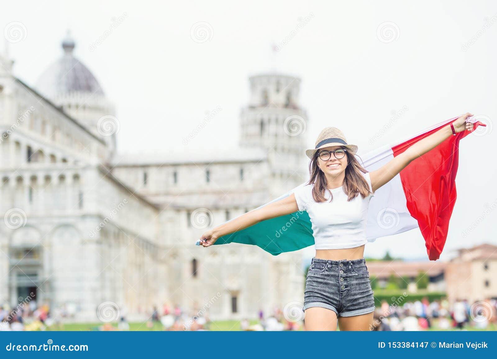Giovane viaggiatore teenager della ragazza con la bandiera italiana prima della torre storica in città Pisa - Italia