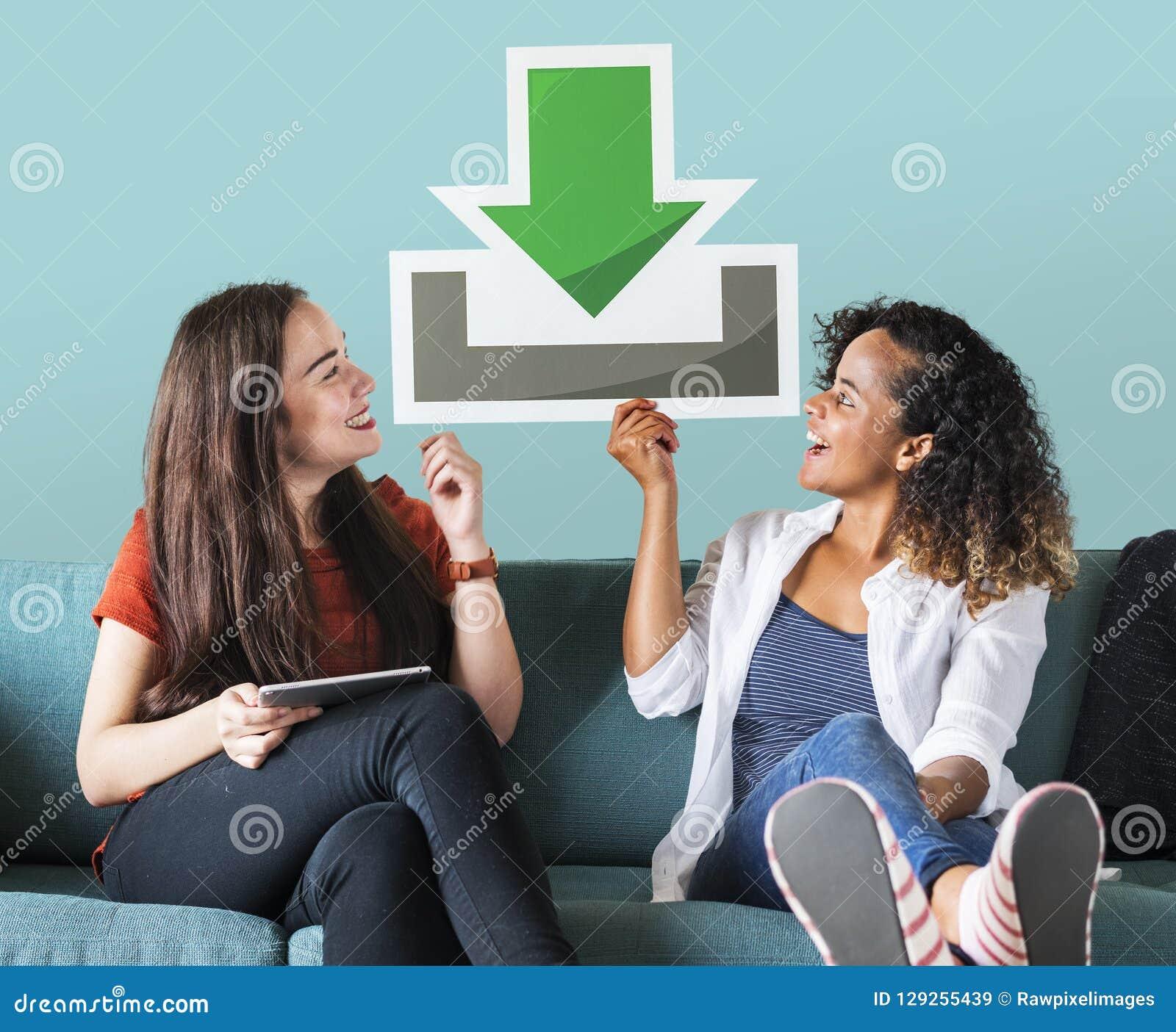Giovani amici femminili che tengono un icona di download