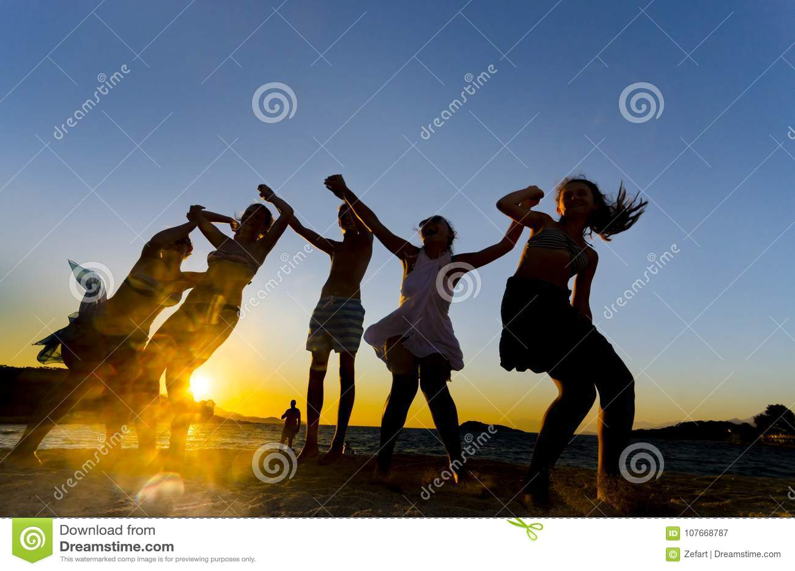 Giovani anni dell adolescenza felici che ballano alla spiaggia al bello tramonto di estate