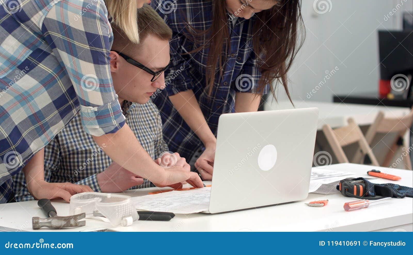 Giovani architetti che controllano le misure del disegno con il divisore