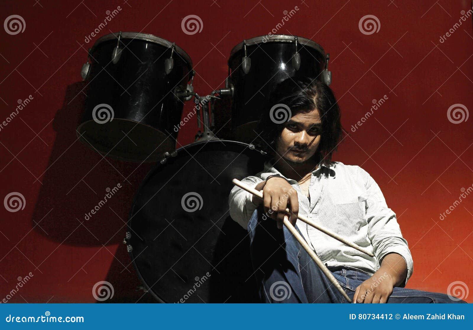 Giovani bastoni e seduta della tenuta del batterista accanto alla batteria