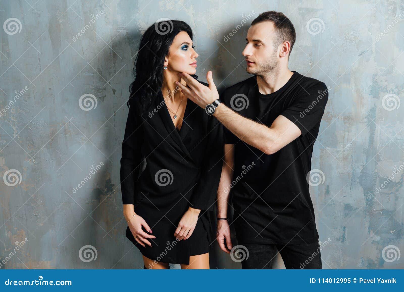 Giovani belle coppie splendide alla moda, contro il sottotetto grigio della parete nello studio o a casa