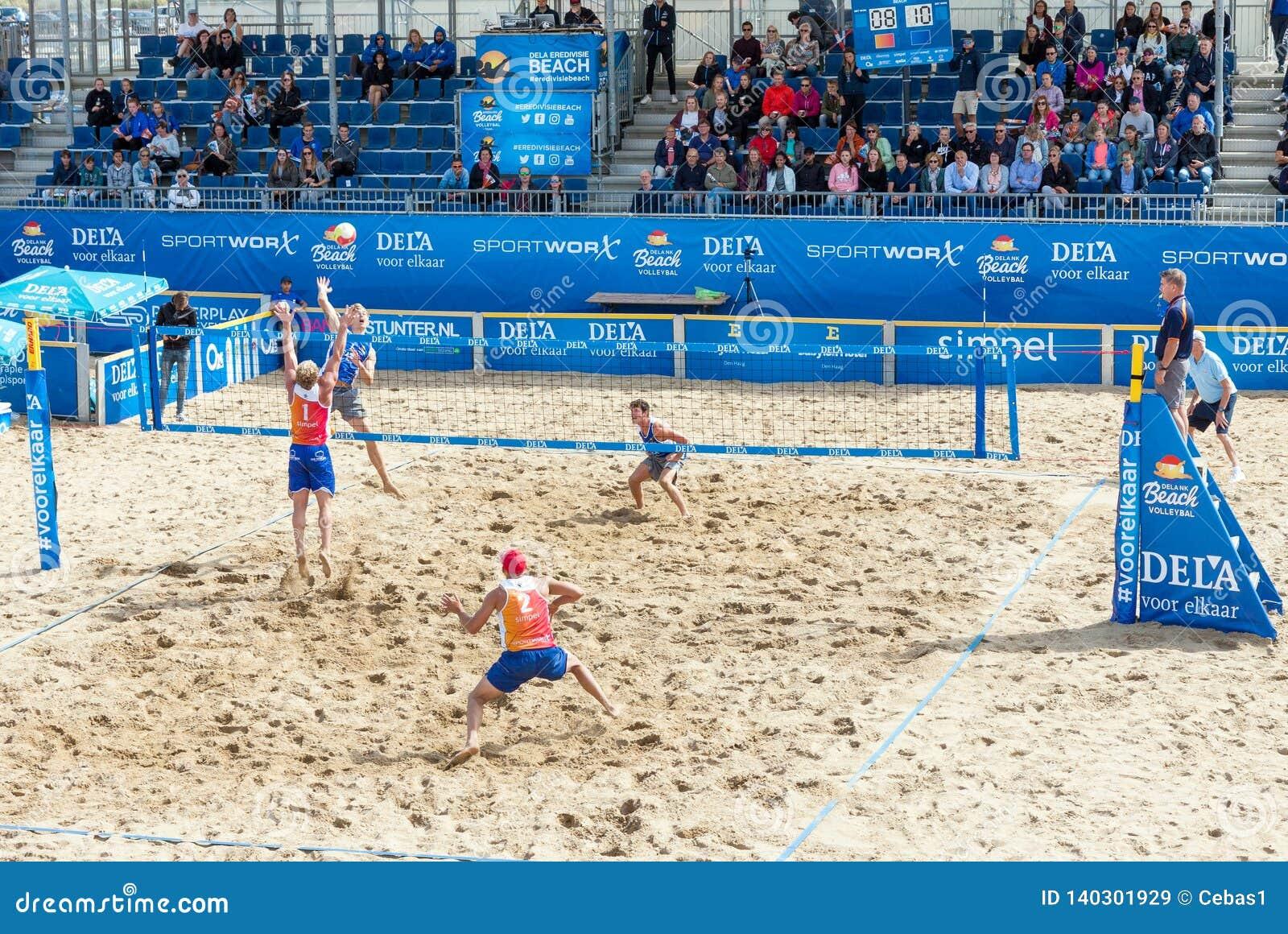 Giovani che giocano la partita professionale di beach volley in arena all aperto