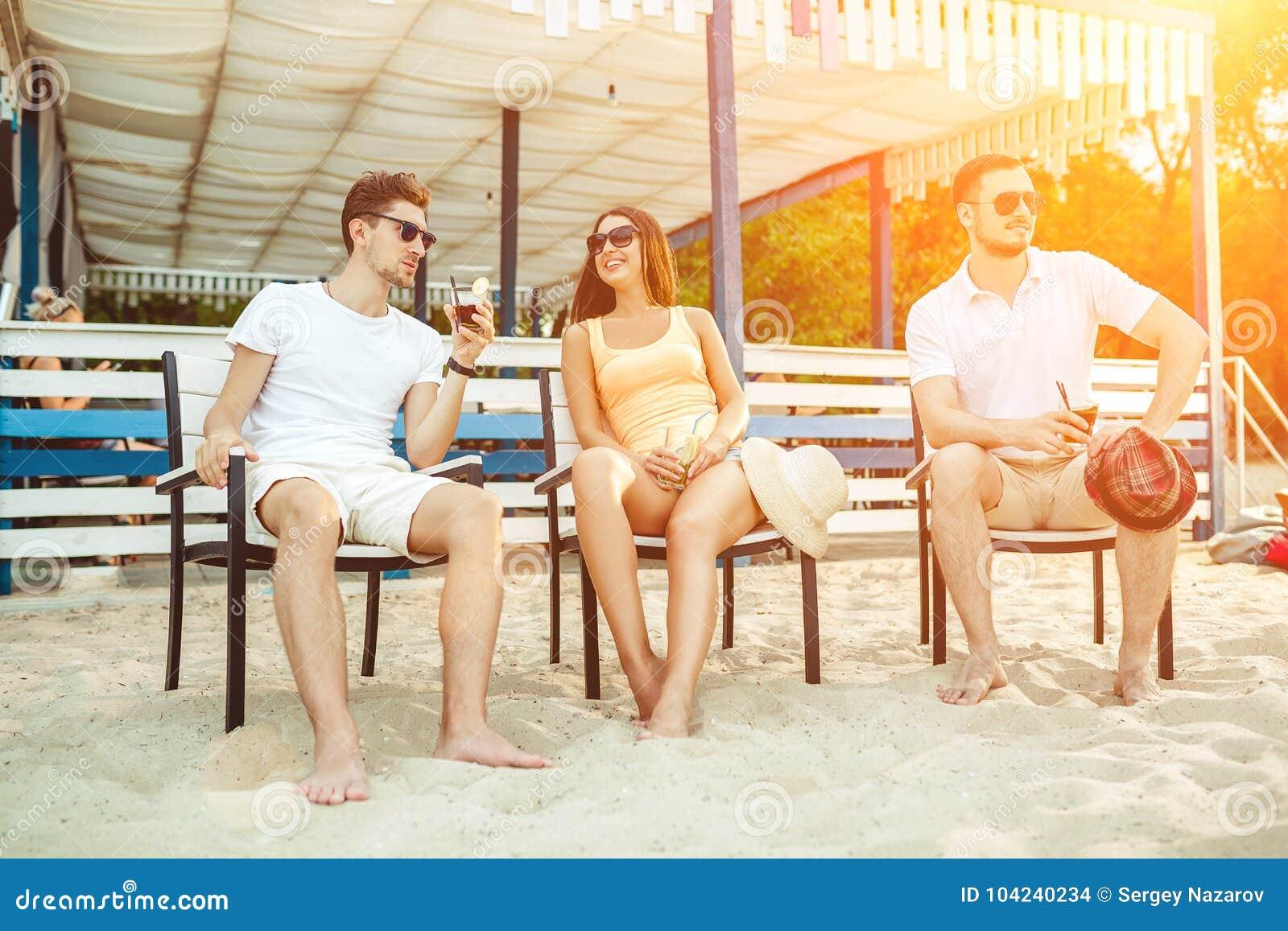 Giovani che godono del bere prendente il sole di vacanze - Alla colorazione della spiaggia ...