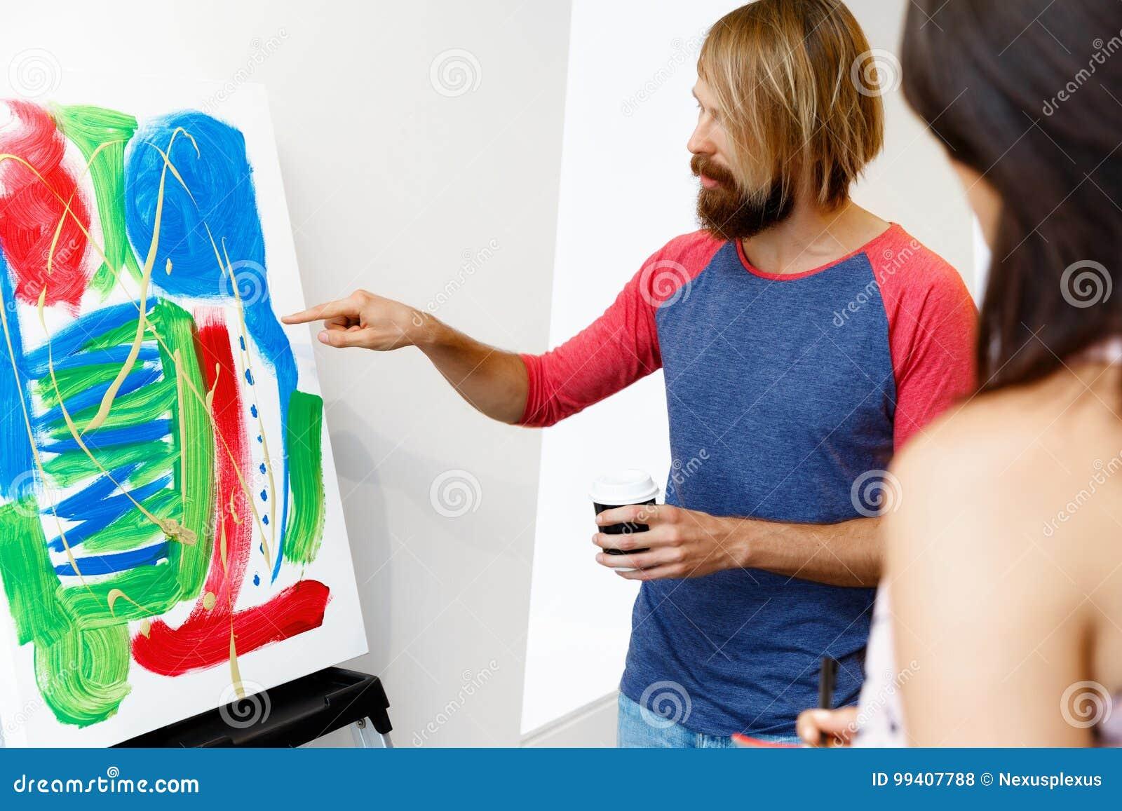 Giovani che stanno in una galleria e che contemplano materiale illustrativo