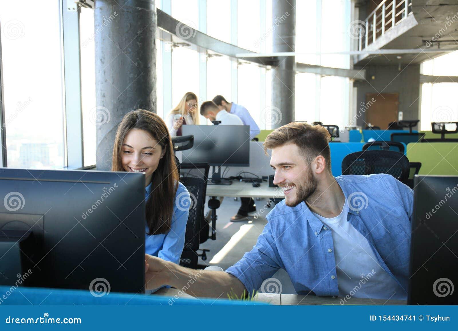 Giovani colleghi moderni nel funzionamento astuto di abbigliamento casual mentre spendendo tempo nell ufficio