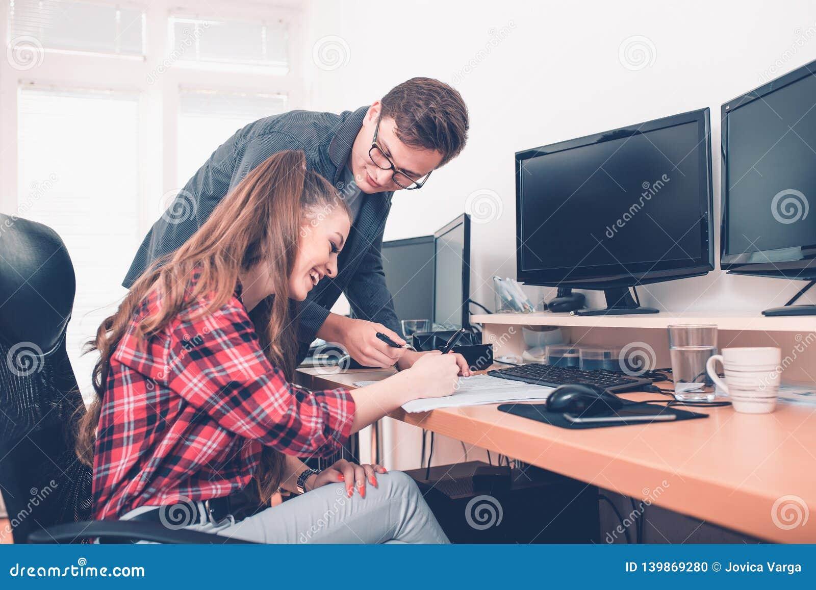 Giovani colleghi sorridenti che lavorano con i documenti in ufficio