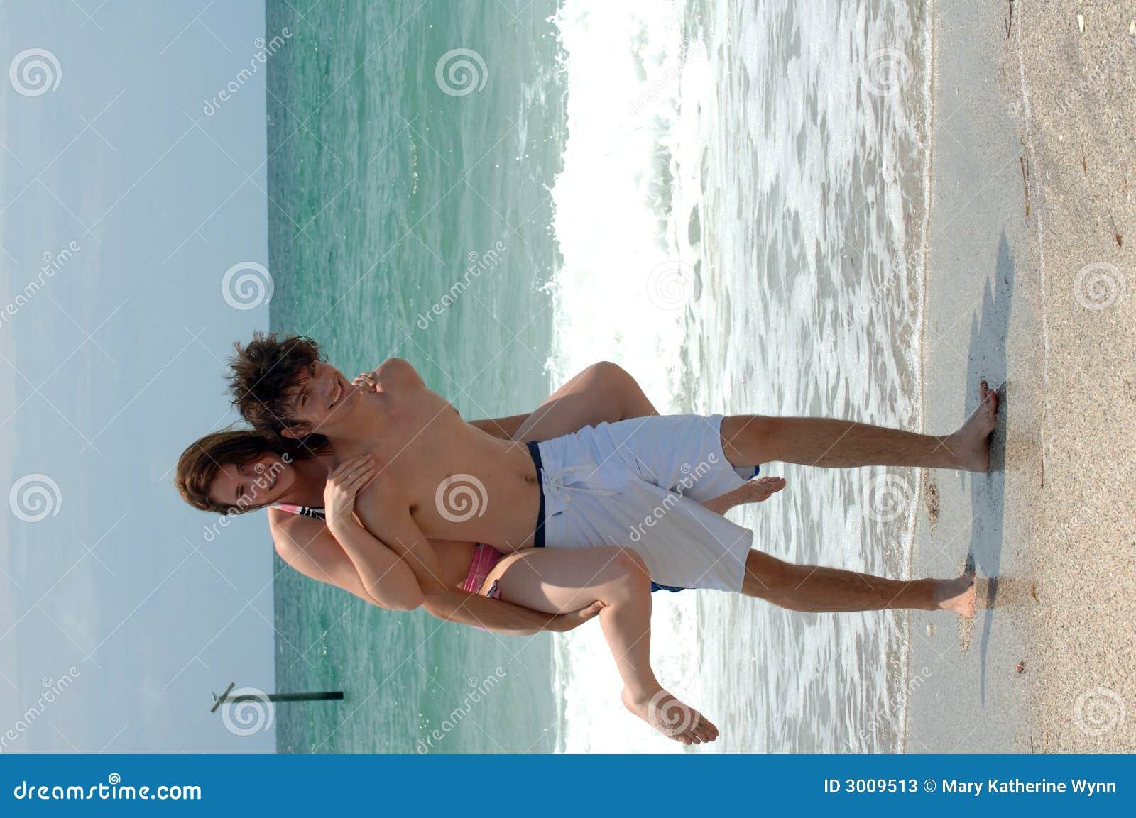 Giovani coppie allegre della spiaggia