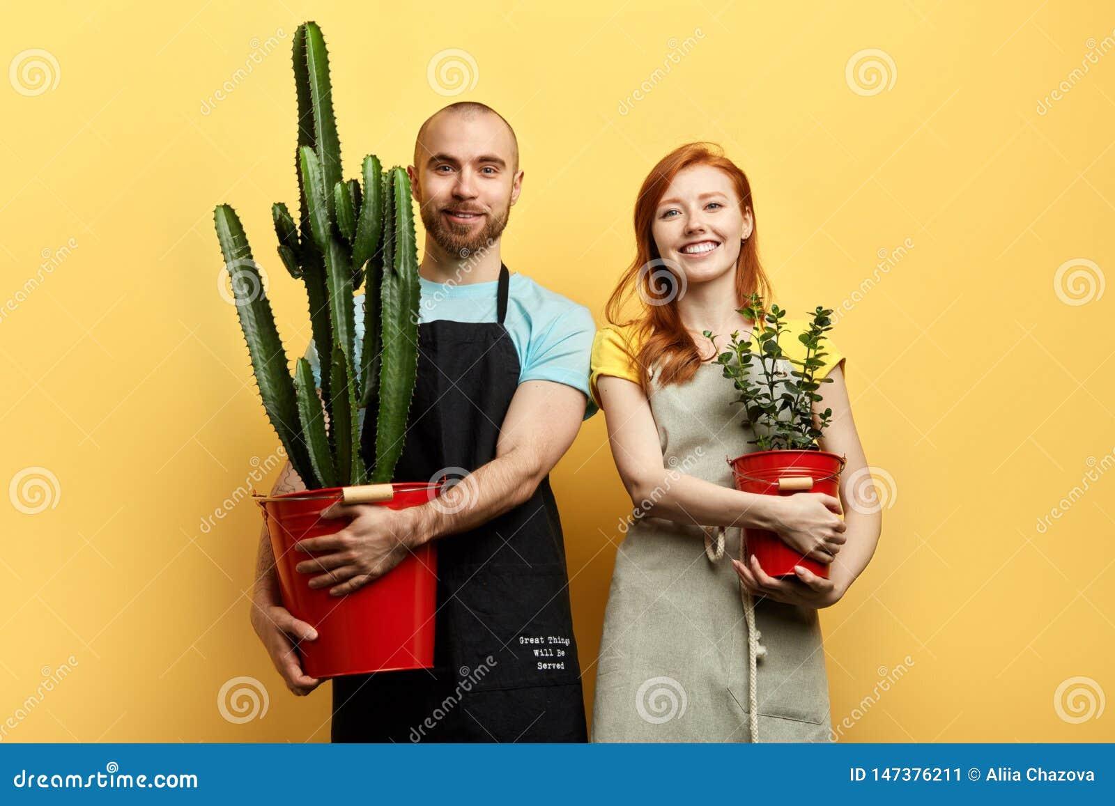 Giovani coppie allegre felici con i fiori che posano alla macchina fotografica