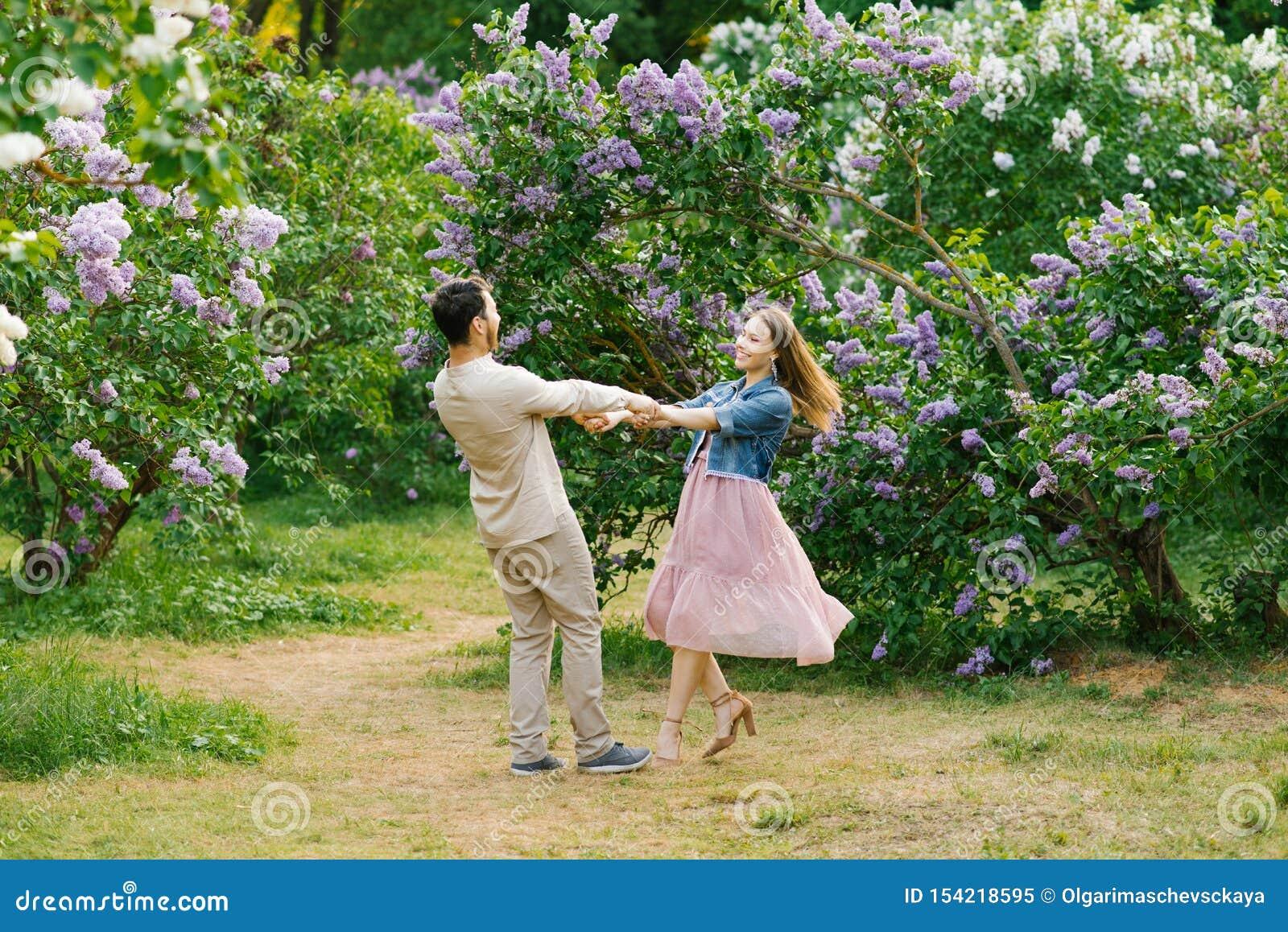 Giovani coppie amorose che si tengono per mano e che filano nel giardino lilla