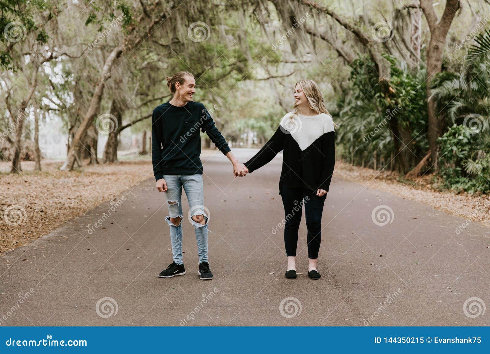 Giovani coppie amorose felici sveglie che camminano giù una vecchia strada abbandonata con sporgersi degli alberi di cerro