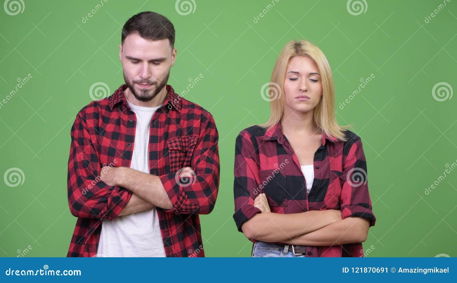 Giovani coppie arrabbiate con gli occhi chiusi e armi attraversate insieme video d archivio