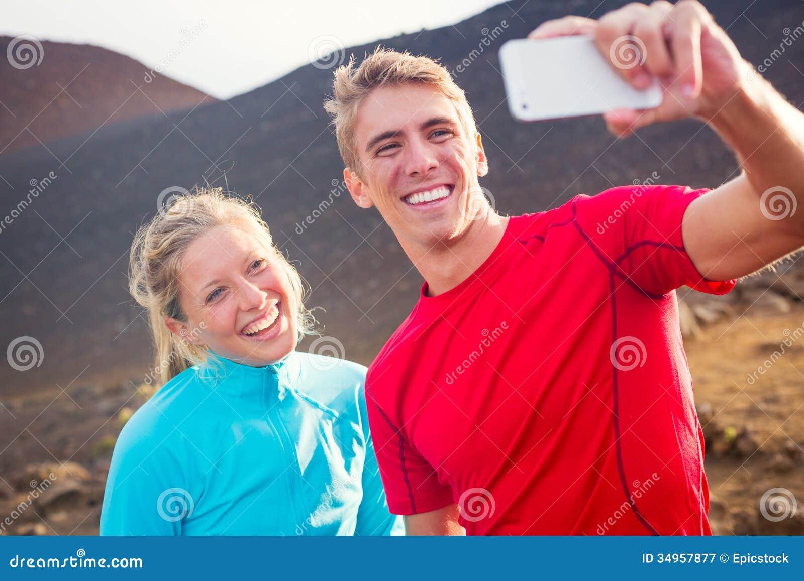 Giovani coppie atletiche attraenti che prendono foto se stessi con