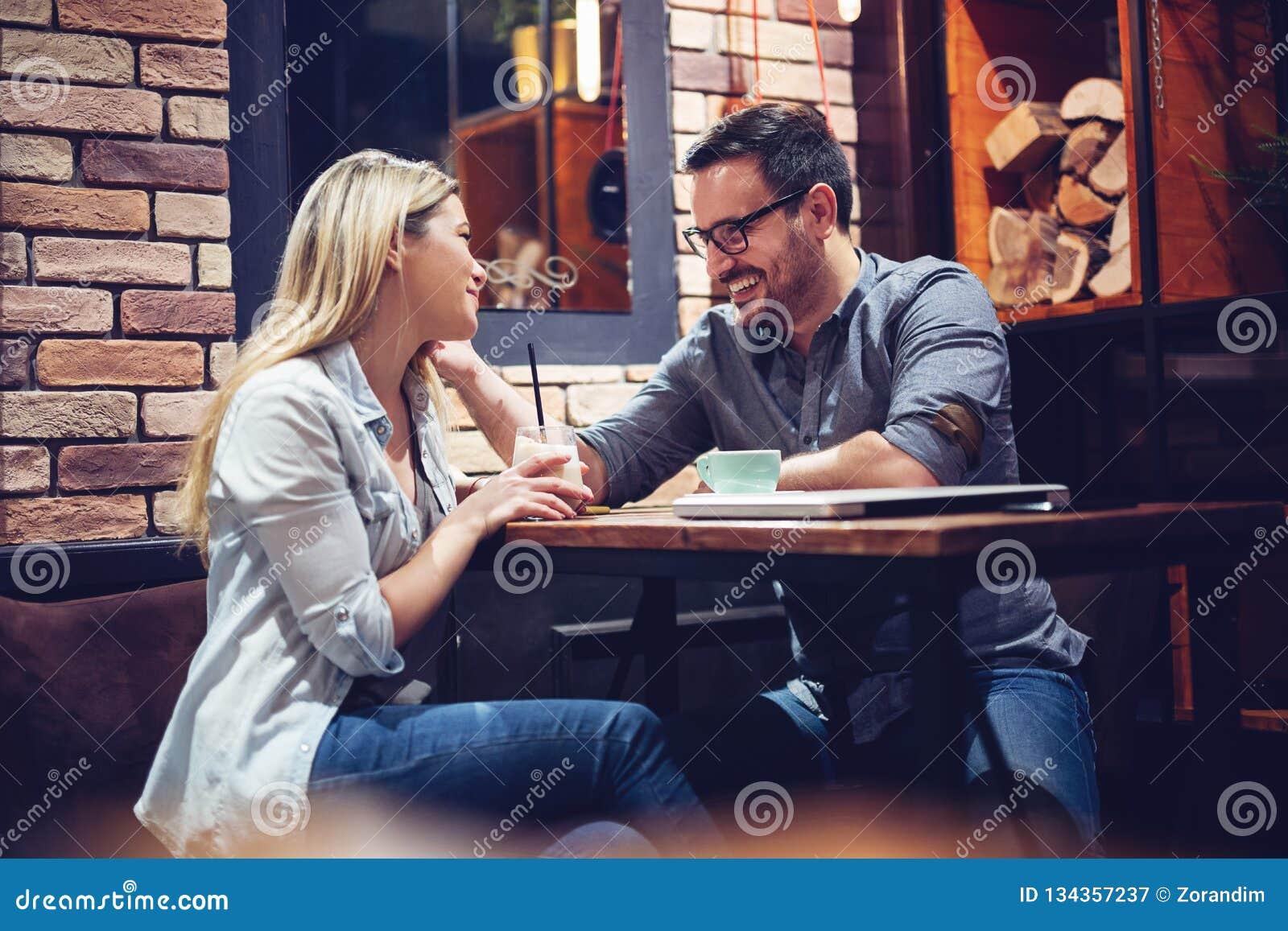 Giovani coppie attraenti che flirtano in caffè