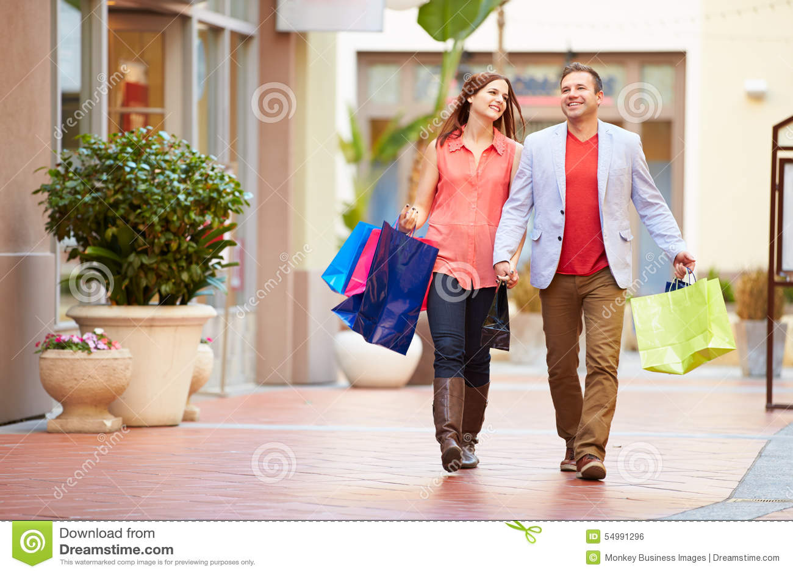 Giovani coppie che camminano attraverso il centro commerciale con i sacchetti della spesa