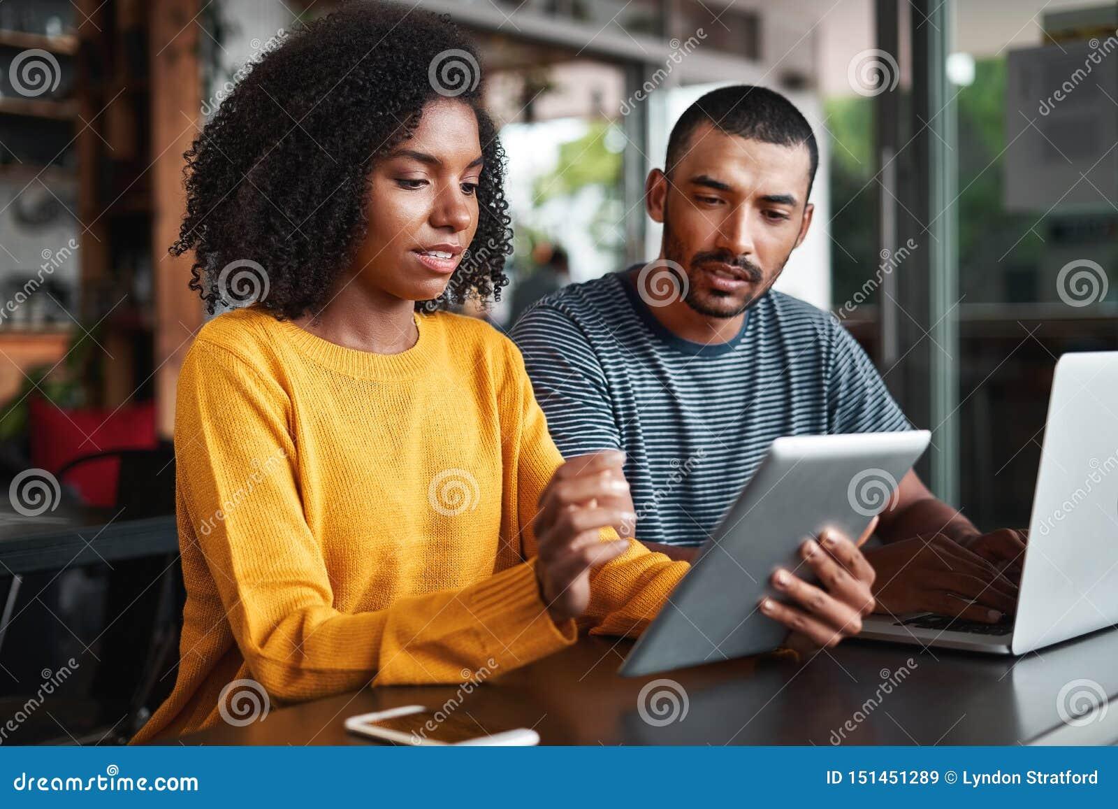Giovani coppie che esaminano compressa digitale in caffè