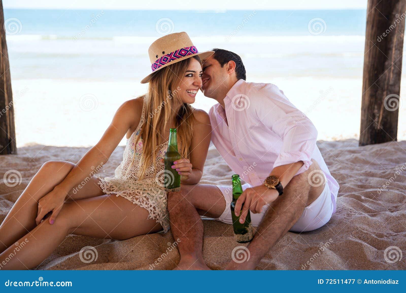 Giovani coppie che flirtano ad a vicenda nella spiaggia