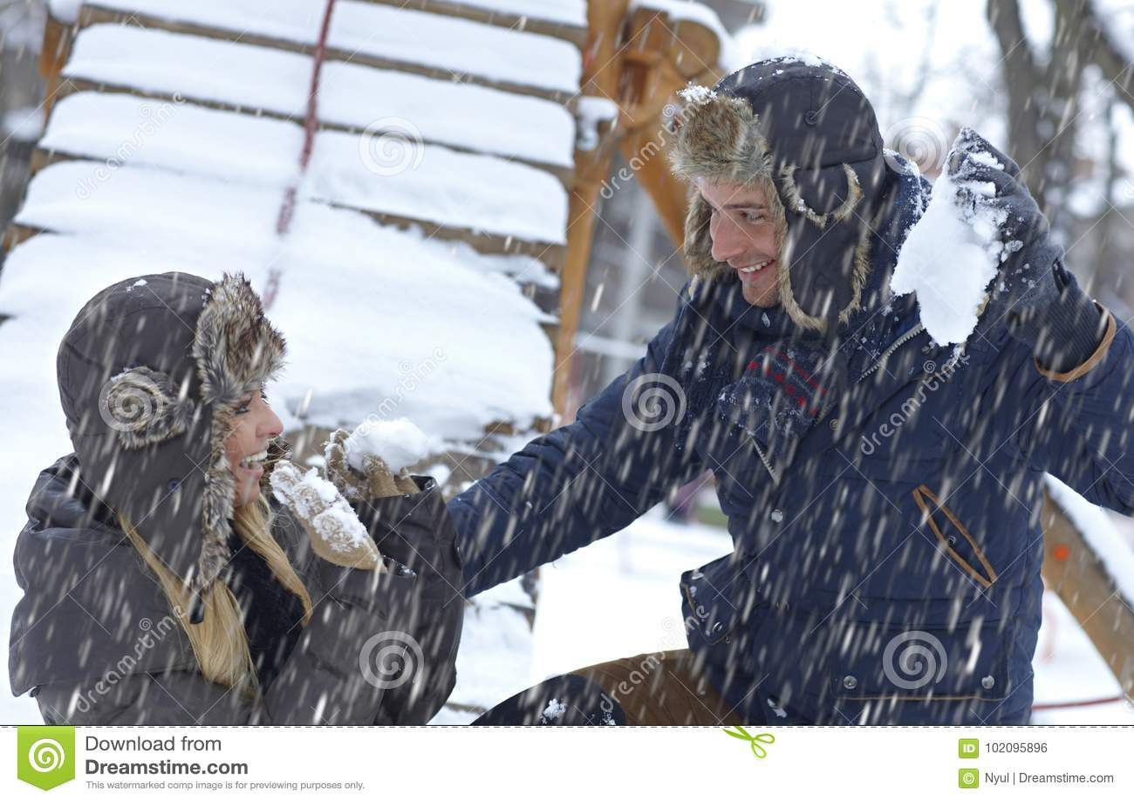 Giovani coppie che giocano in precipitazioni nevose