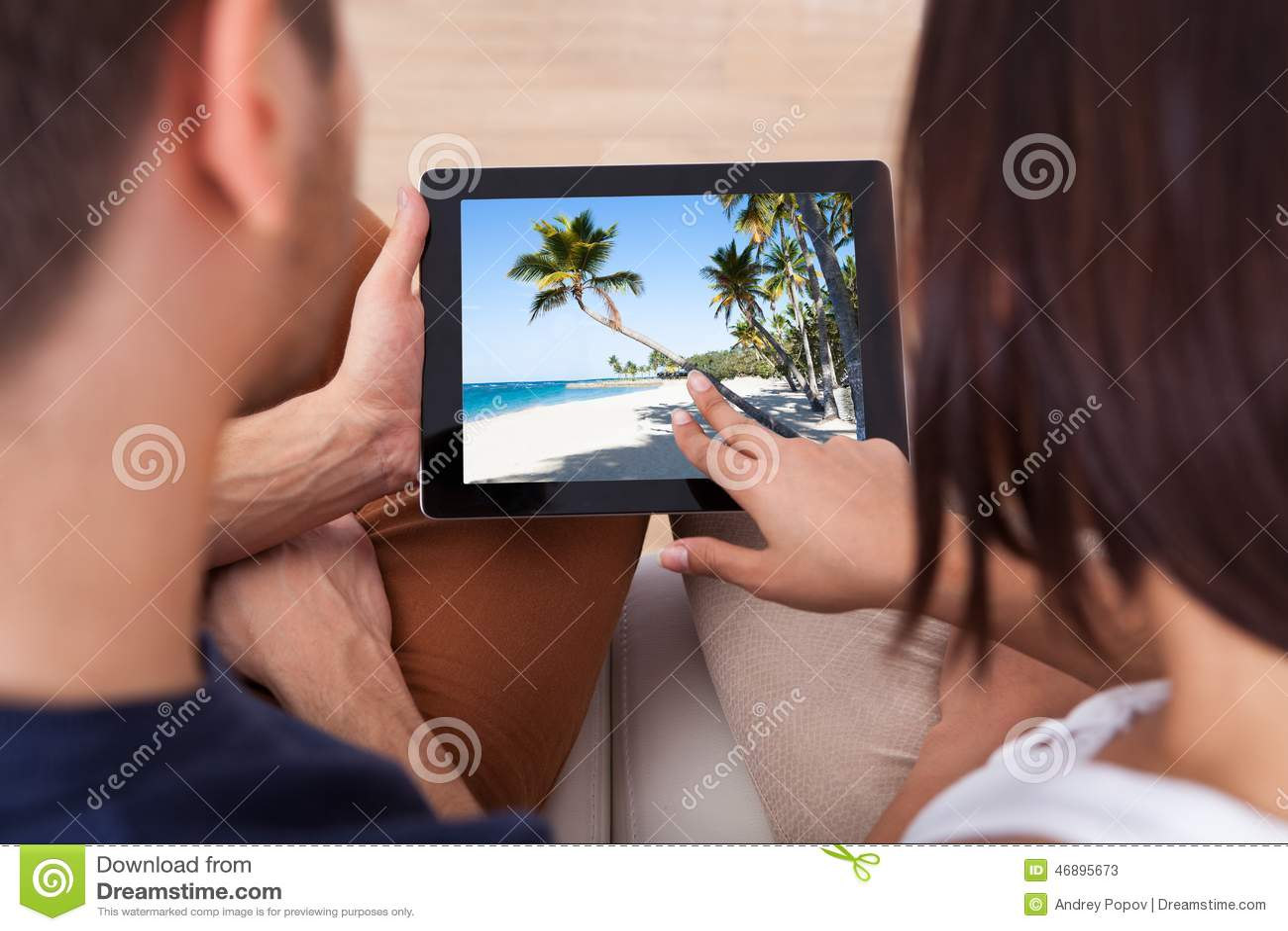 Giovani coppie che guardano insieme le foto sulla compressa digitale