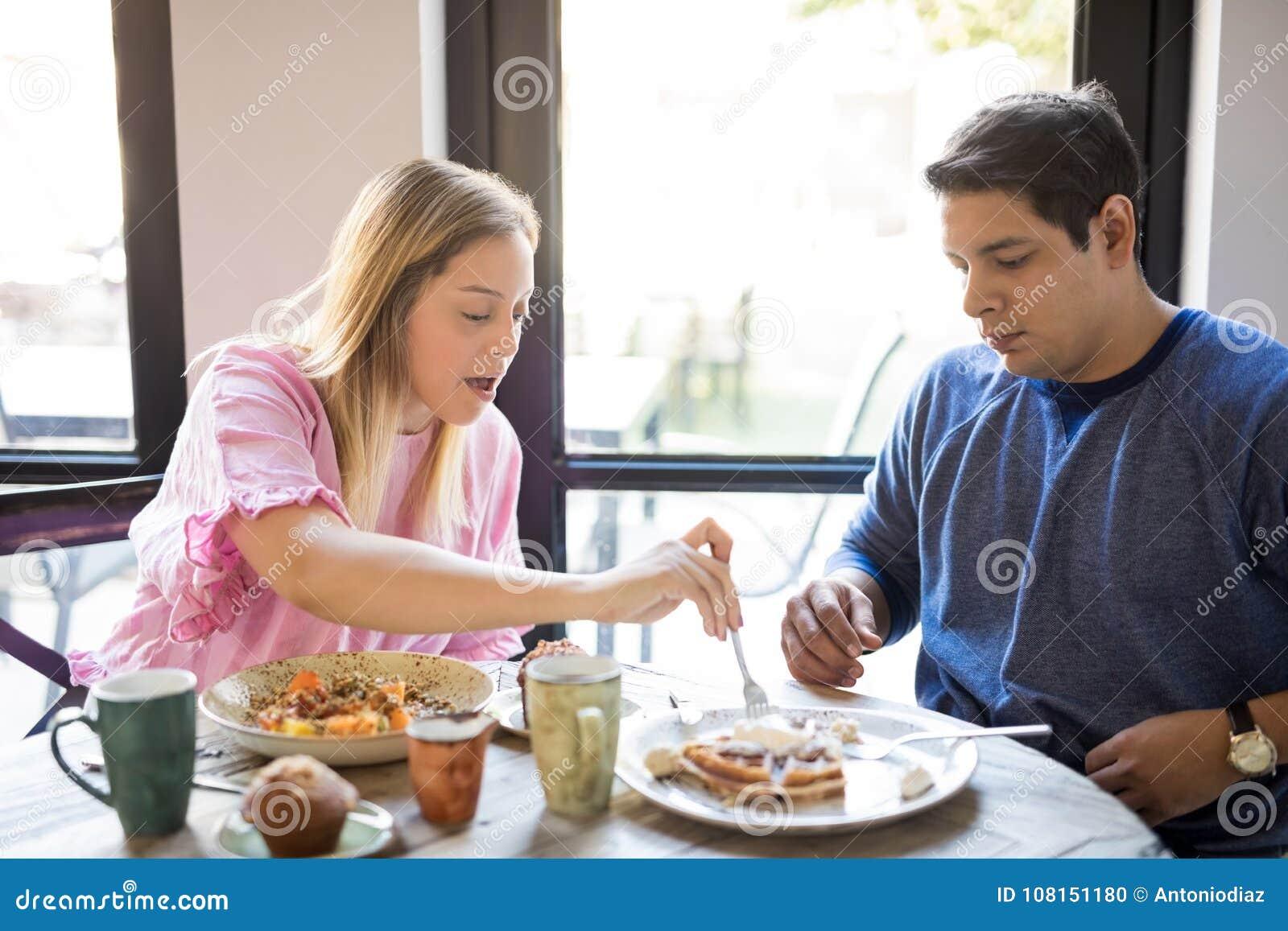Giovani coppie che mangiano prima colazione in un ristorante