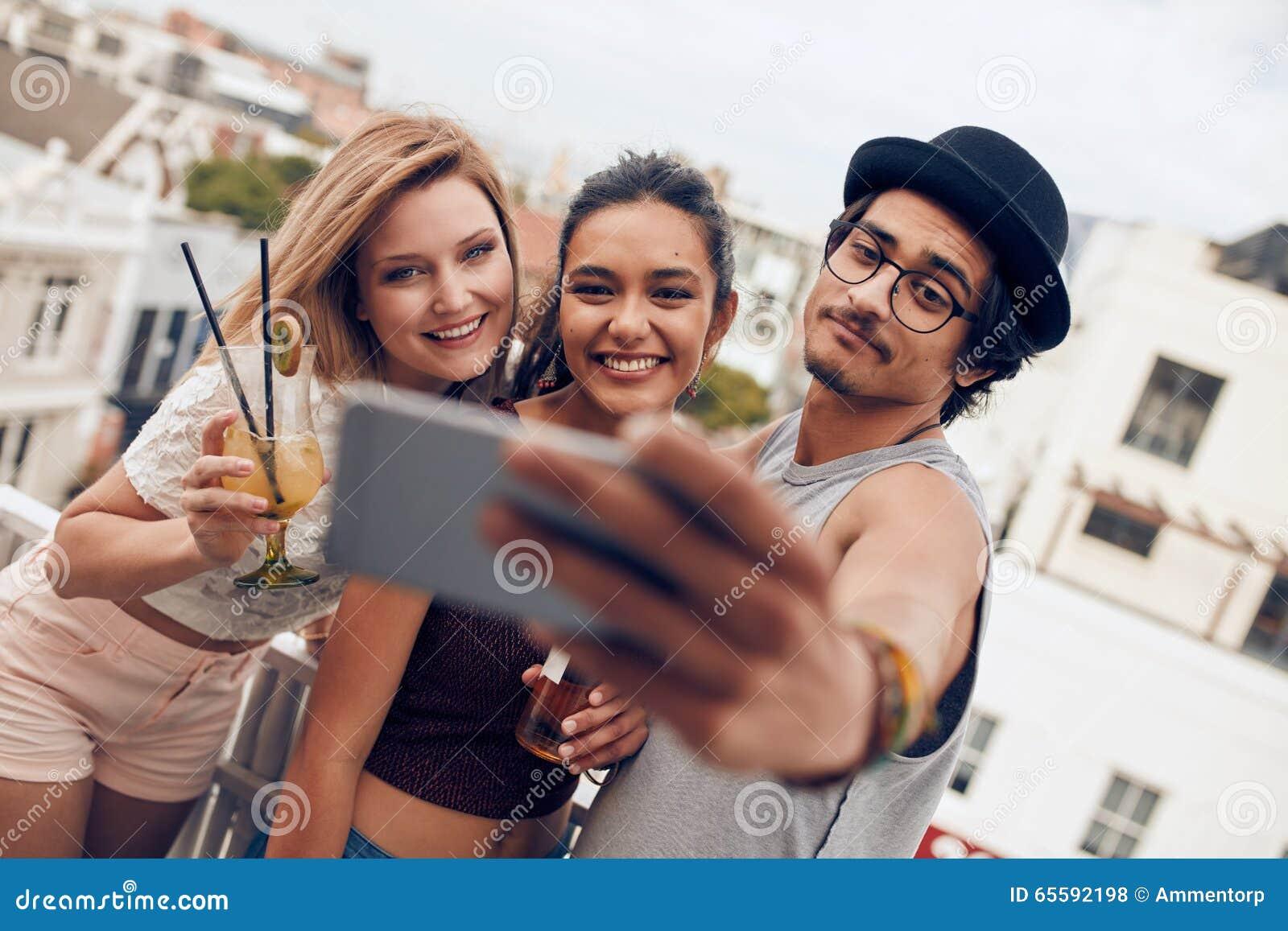 Giovani coppie che prendono un selfie sul tetto
