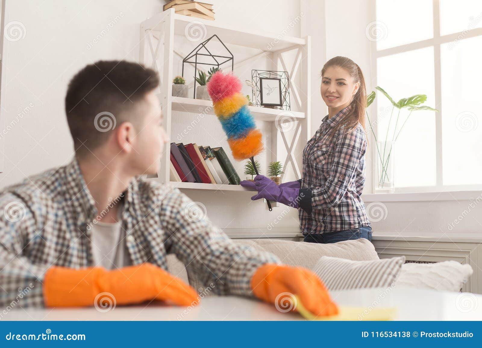 Giovani coppie che puliscono insieme polvere