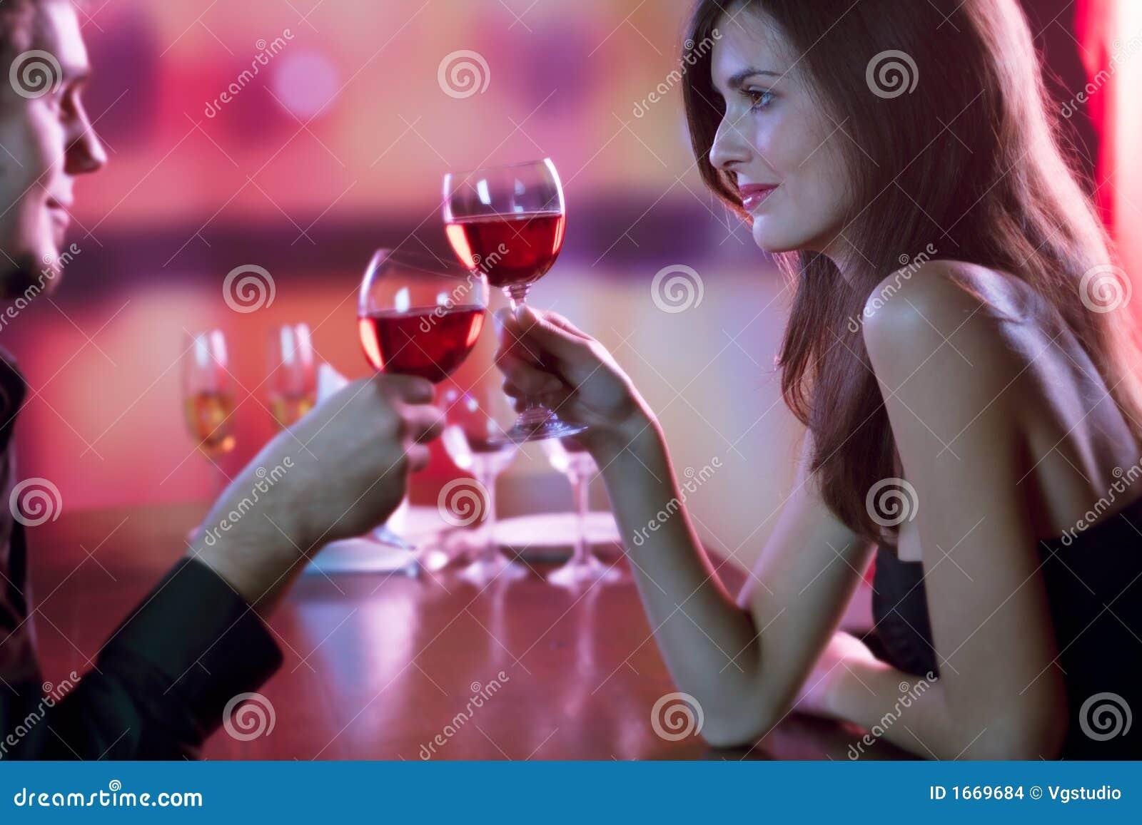 Giovani coppie che ripartono un vetro di vino rosso in ristorante, celebrat