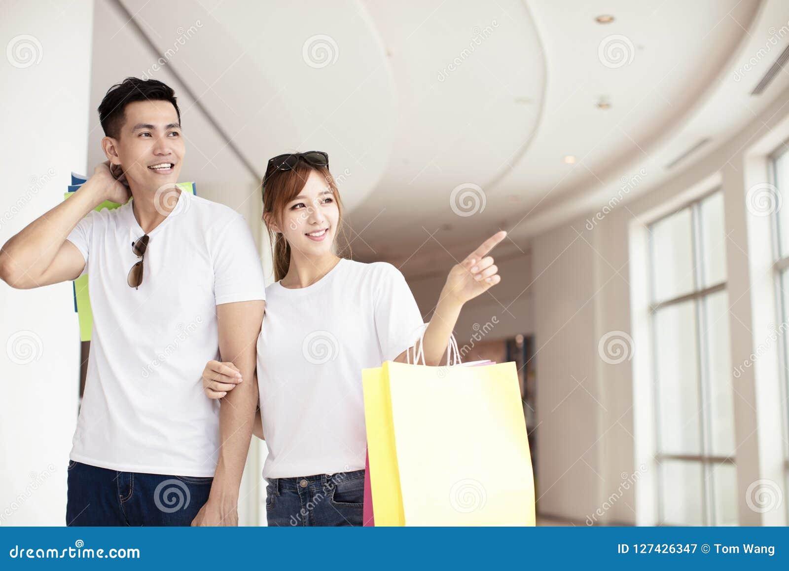 Giovani coppie con i sacchetti della spesa che camminano nel centro commerciale
