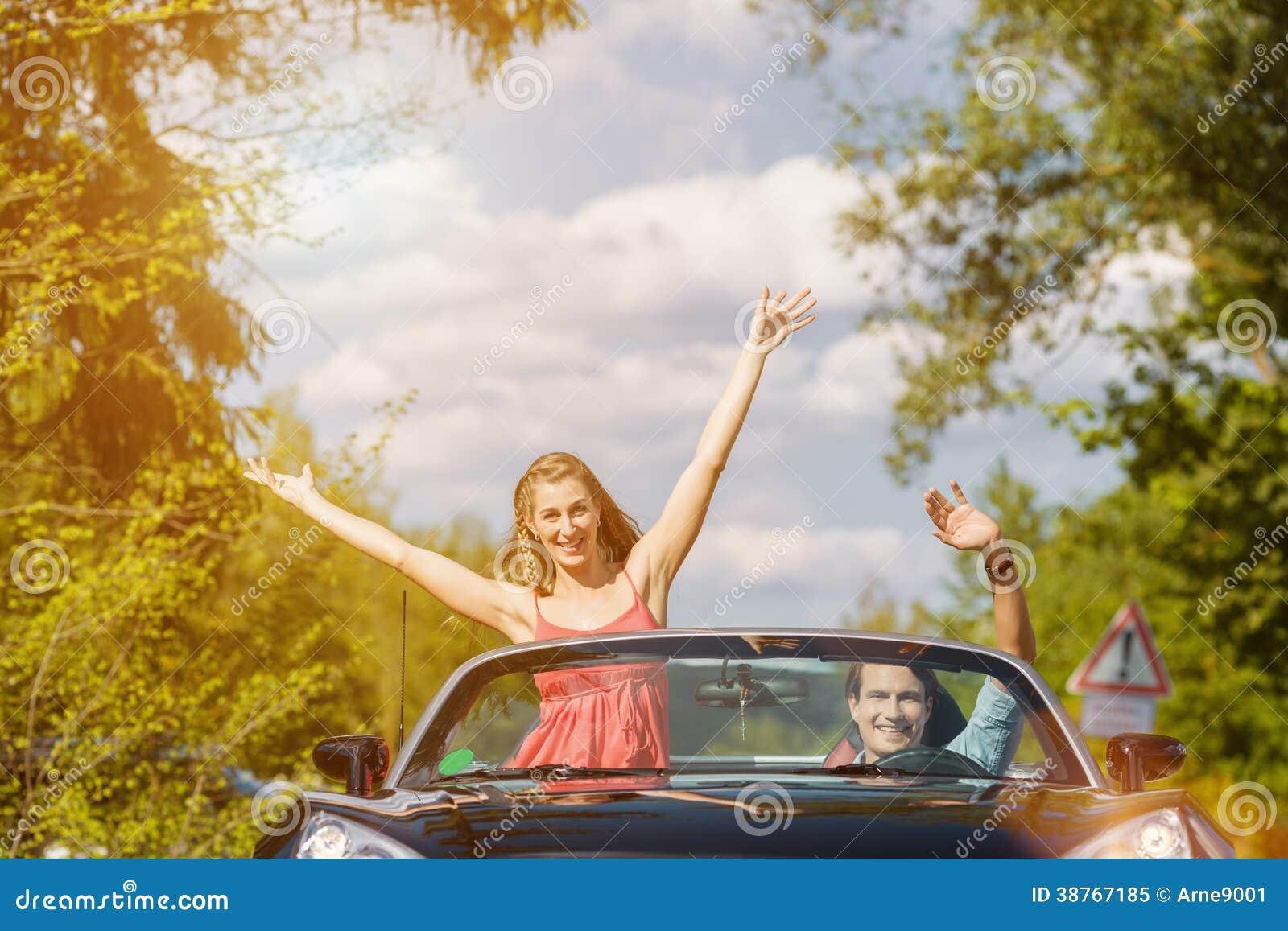 Giovani coppie con l automobile del cabriolet in primavera