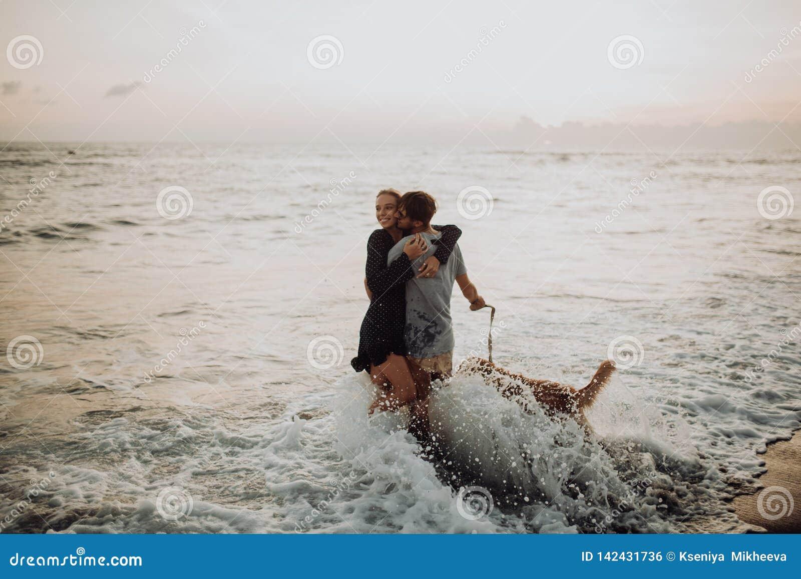 Giovani coppie dei pantaloni a vita bassa di bella risata felice con il golden retriever sulla spiaggia oceano una sabbia Onde co