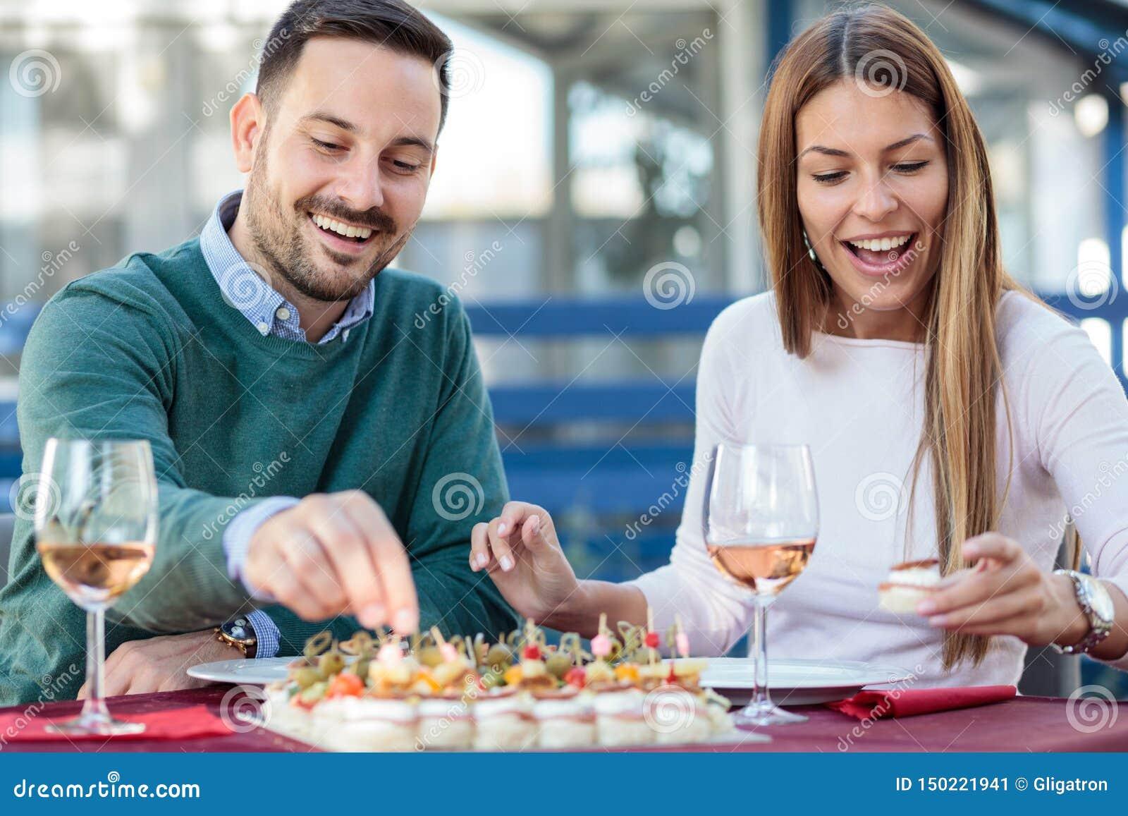 Giovani coppie felici che godono degli aperitivi e che bevono vino rosato prima di pranzare