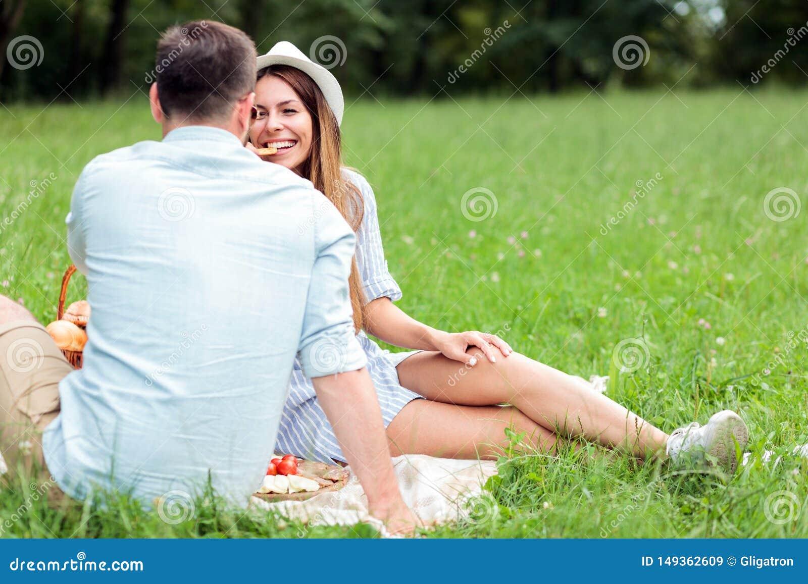 Giovani coppie felici che si divertono in un parco, sedentesi su una coperta di picnic