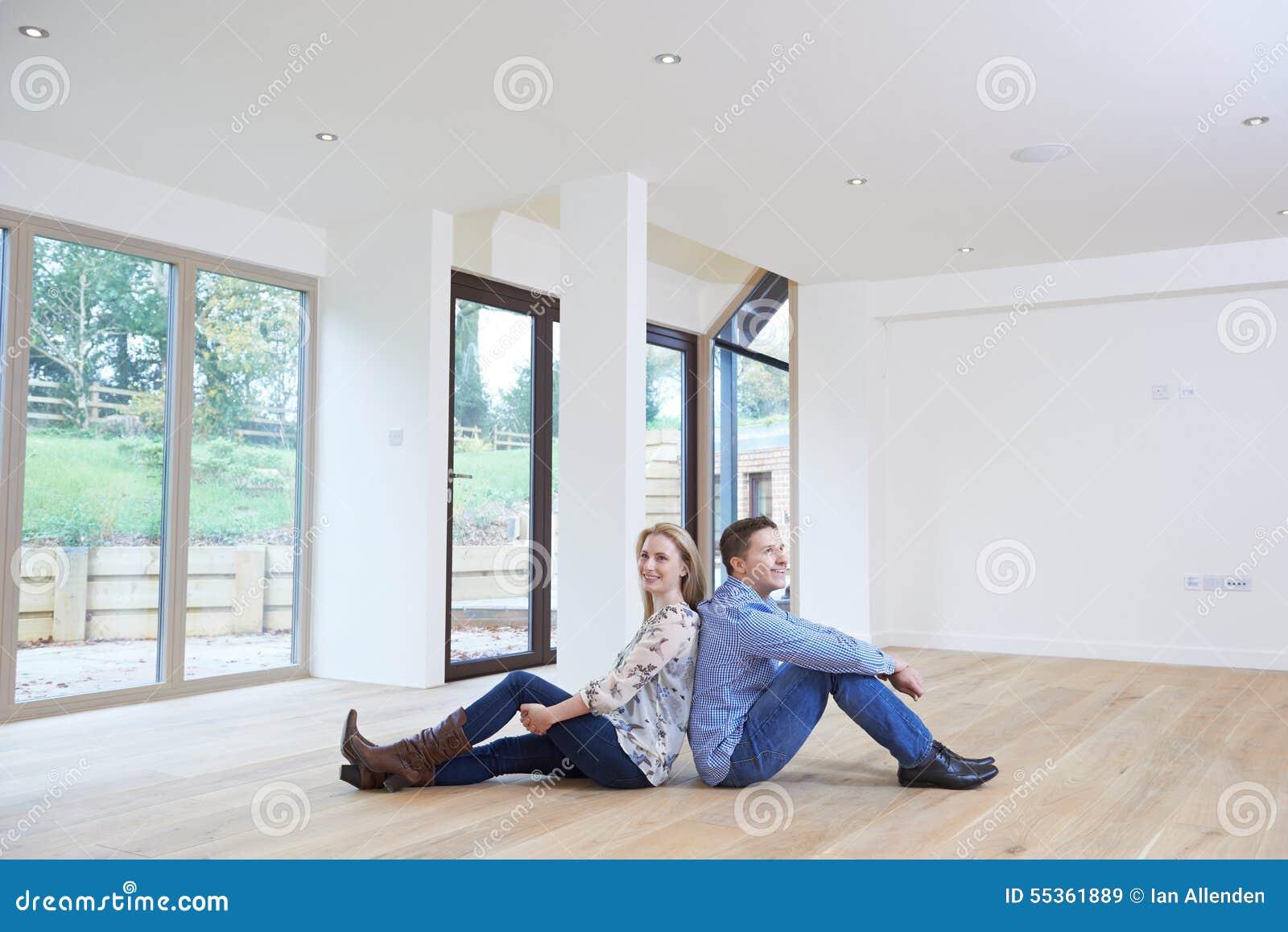 Giovani coppie felici che si siedono sul pavimento nella nuova casa