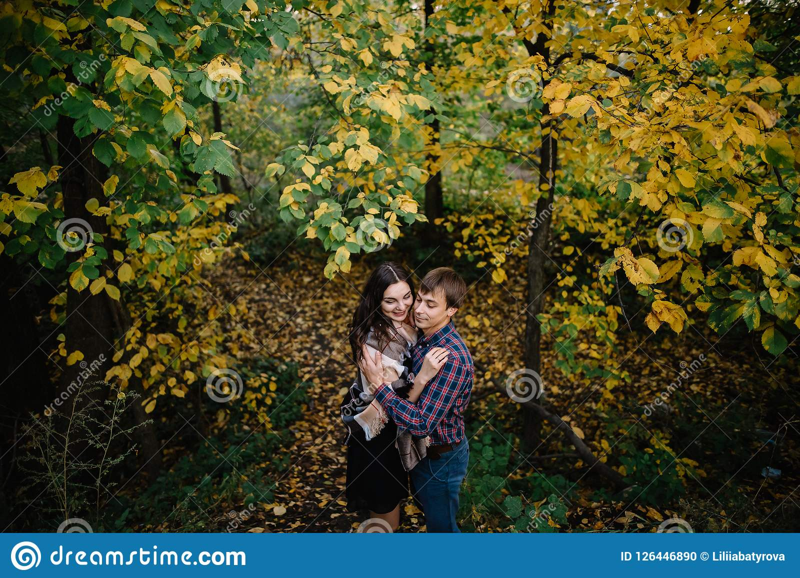 Giovani coppie felici che sorridono e che ridono nella foresta di autunno