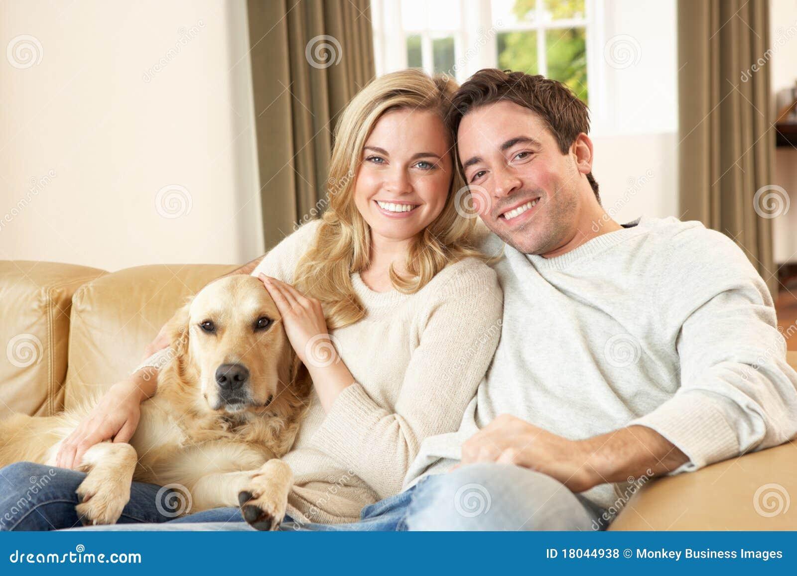Giovani coppie felici con il cane che si siede sul sofà