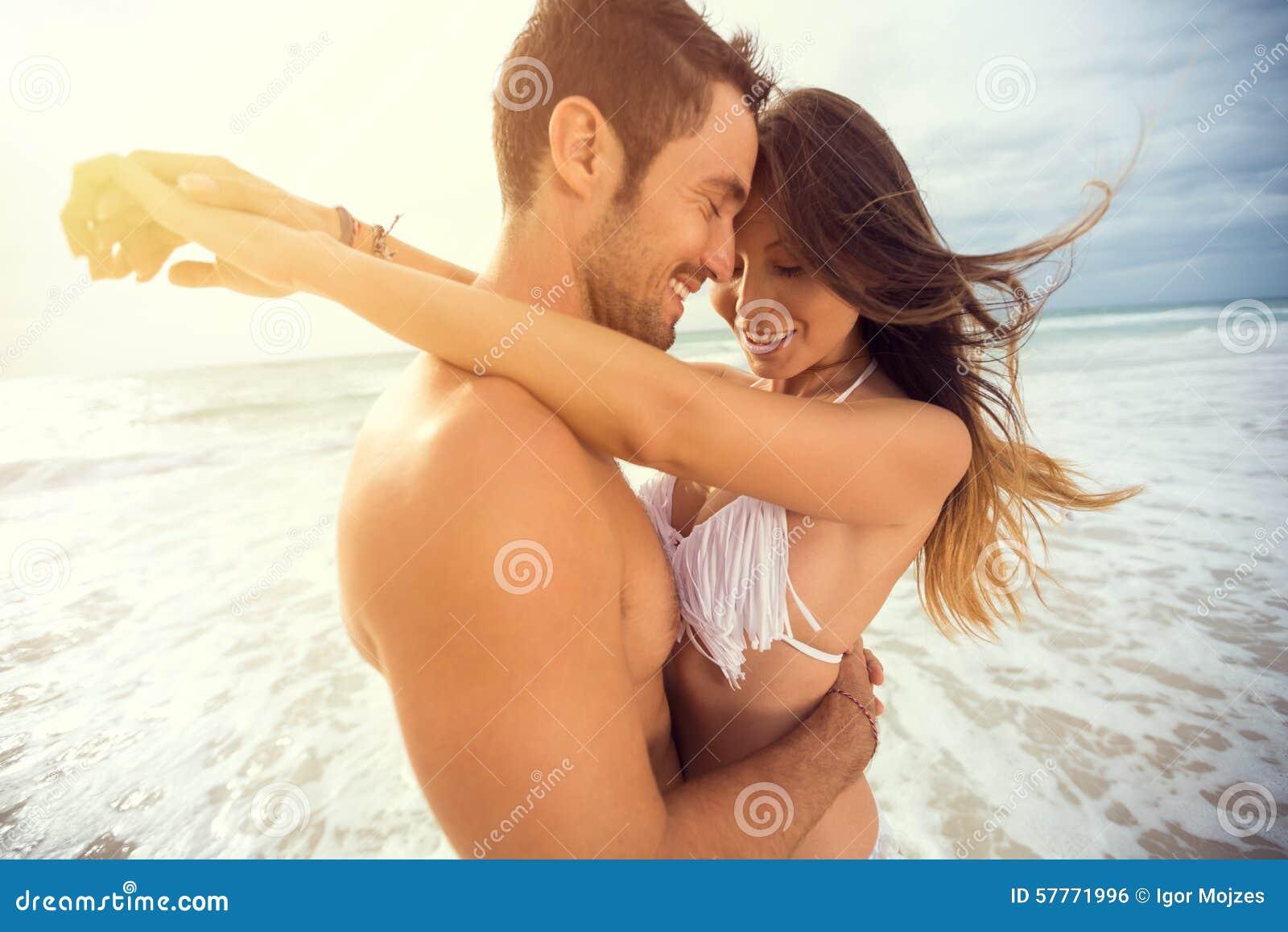Giovani coppie felici con il cuore di tiraggio sulla spiaggia tropicale