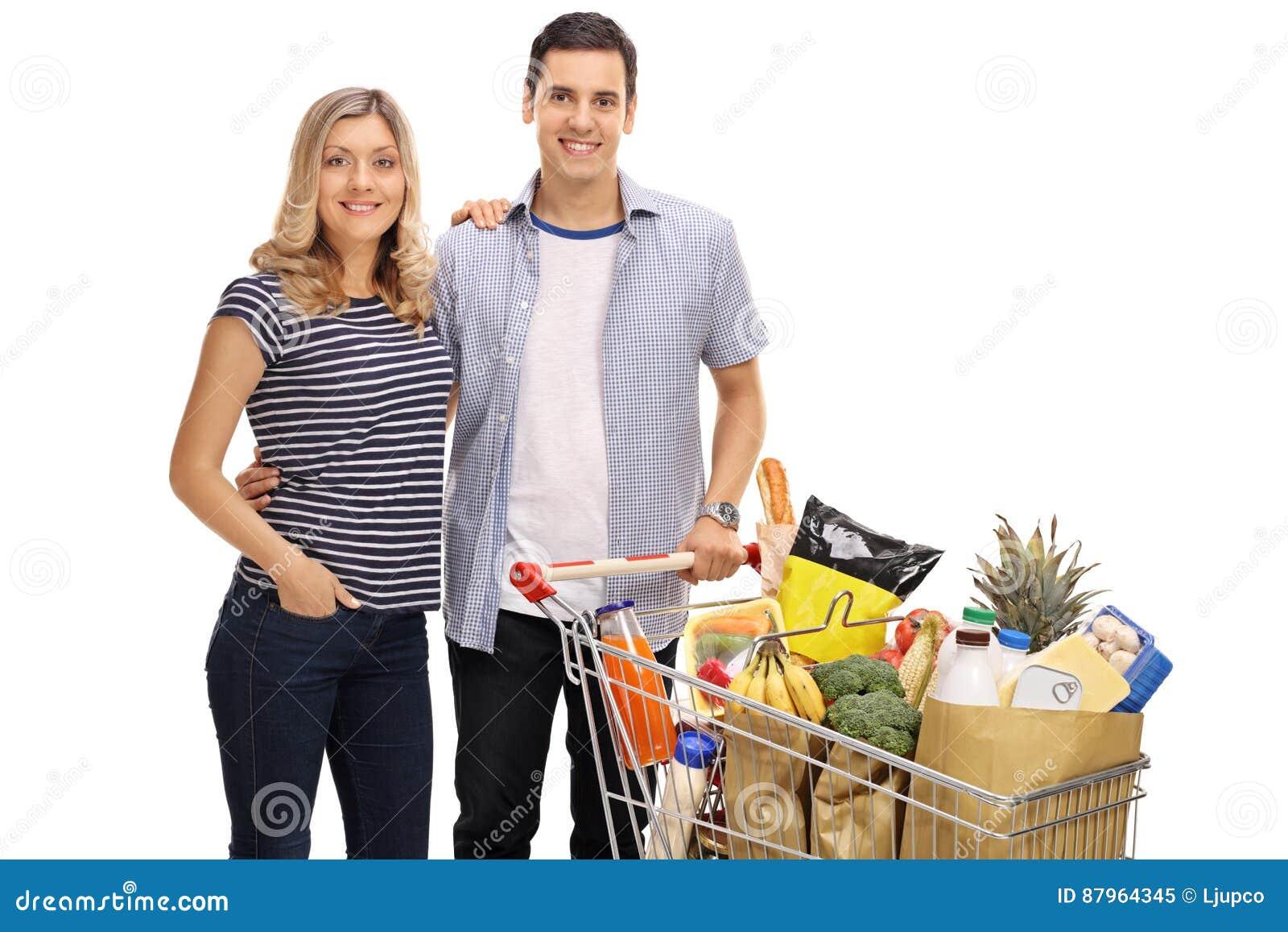 Giovani coppie felici con un carrello pieno delle drogherie