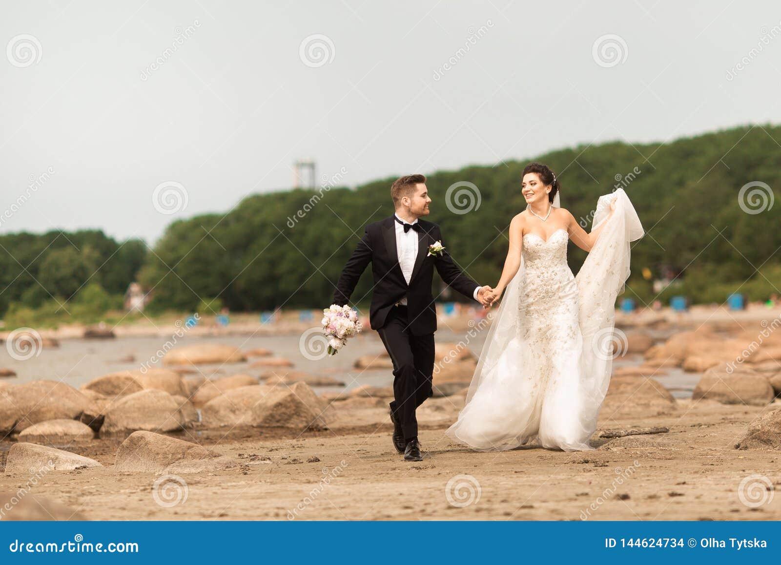 Giovani coppie felici di nozze divertendosi sulla spiaggia