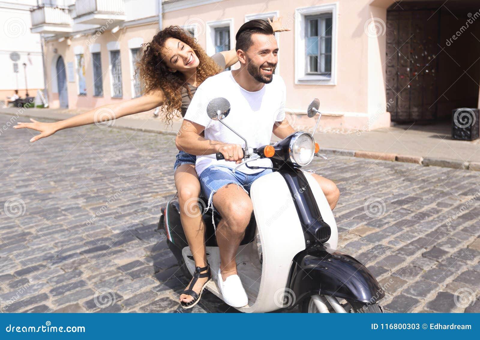 Giovani coppie felici divertendosi su un motorino