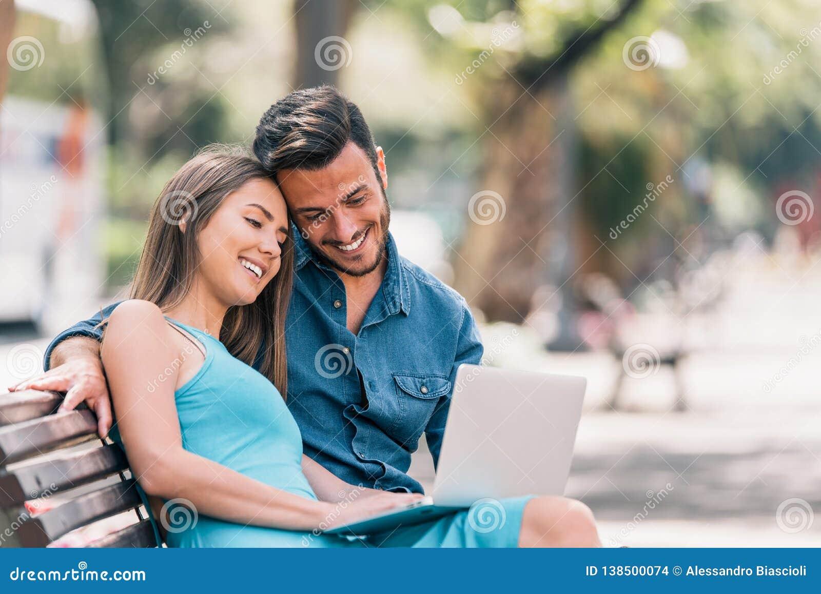 Giovani coppie felici facendo uso del computer portatile che si siede su un banco in città all aperto - due amanti divertendosi s