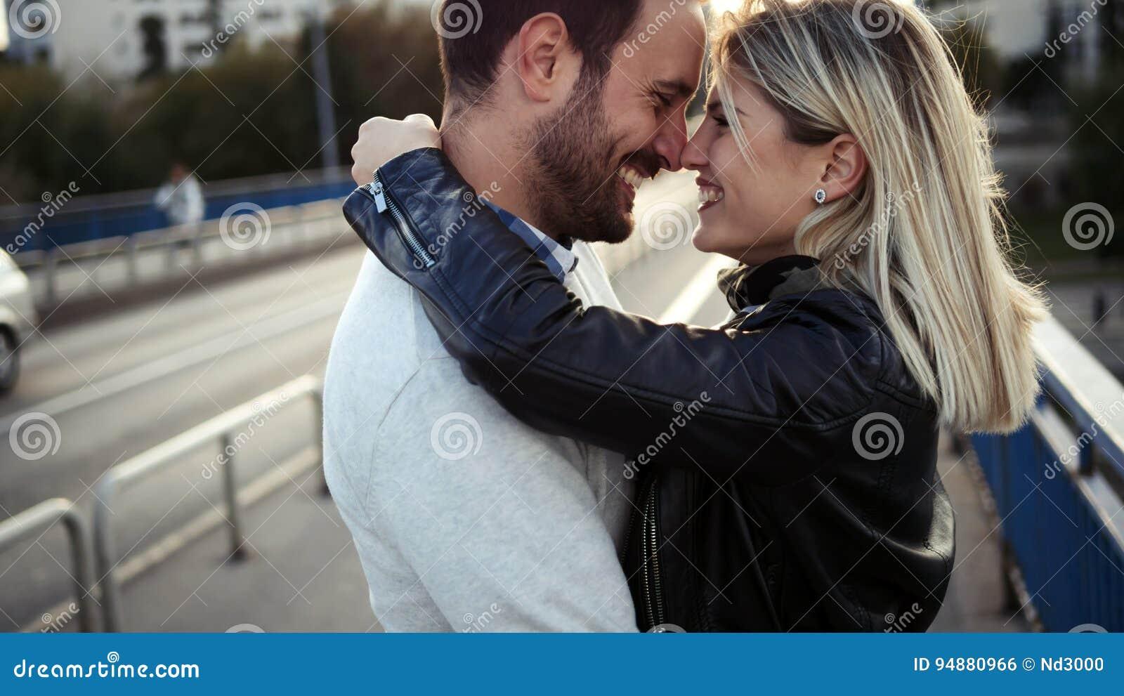Giovani coppie felici romantiche che baciano e che abbracciano