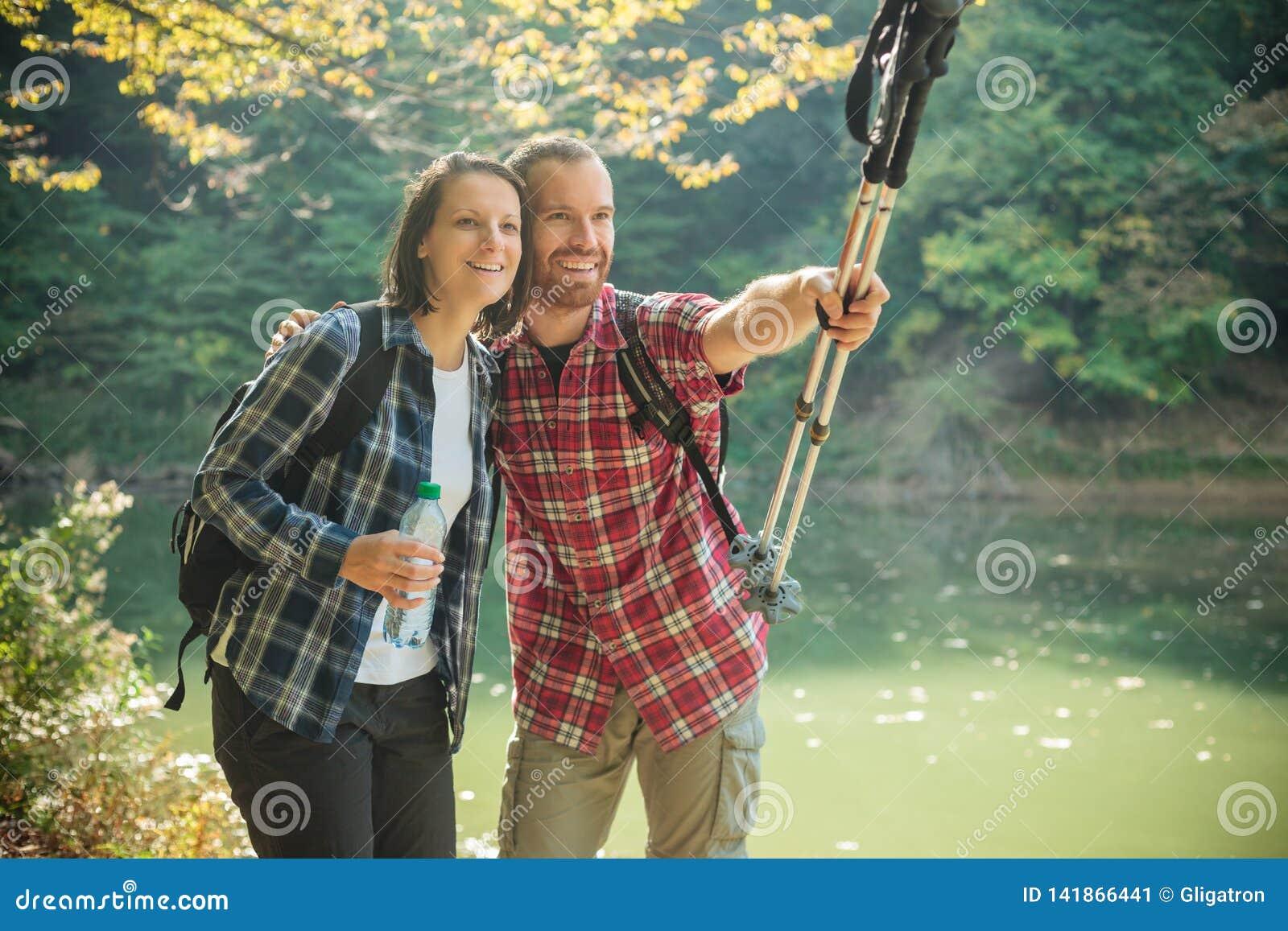 Giovani coppie felici sorridenti che fanno un escursione lungo la riva del lago, abbracciantesi