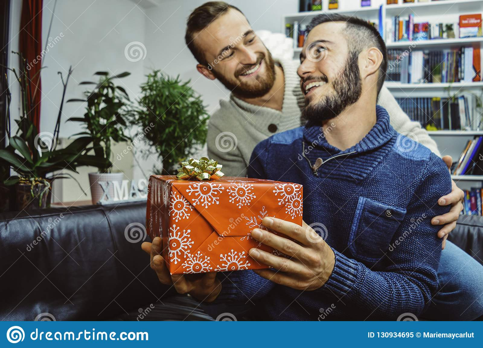 Giovani coppie gay belle sorridenti felici nell amore che se esamina che celebra e che dà regalo