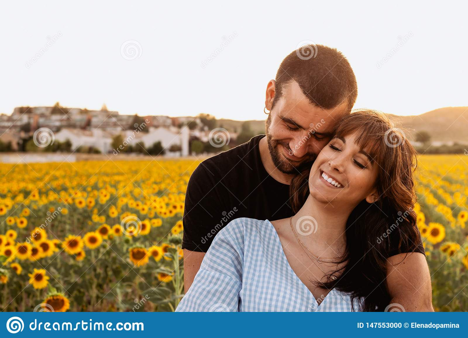 Giovani coppie nell amore che si abbraccia nel giacimento del girasole al tramonto