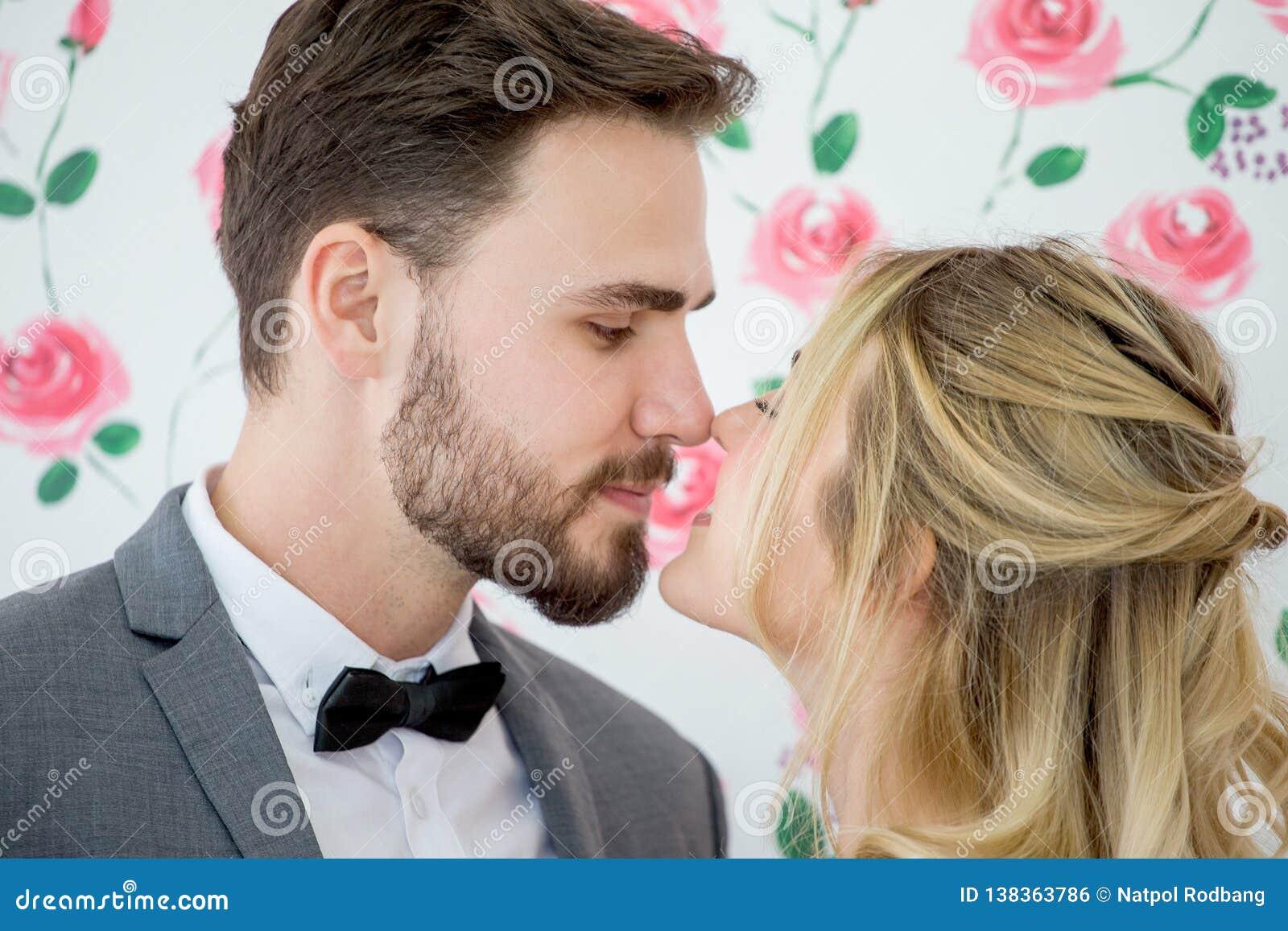 Giovani coppie nella sposa e nello sposo di nozze di amore che baciano sul contesto delle rose newlyweds Ritratto del primo piano